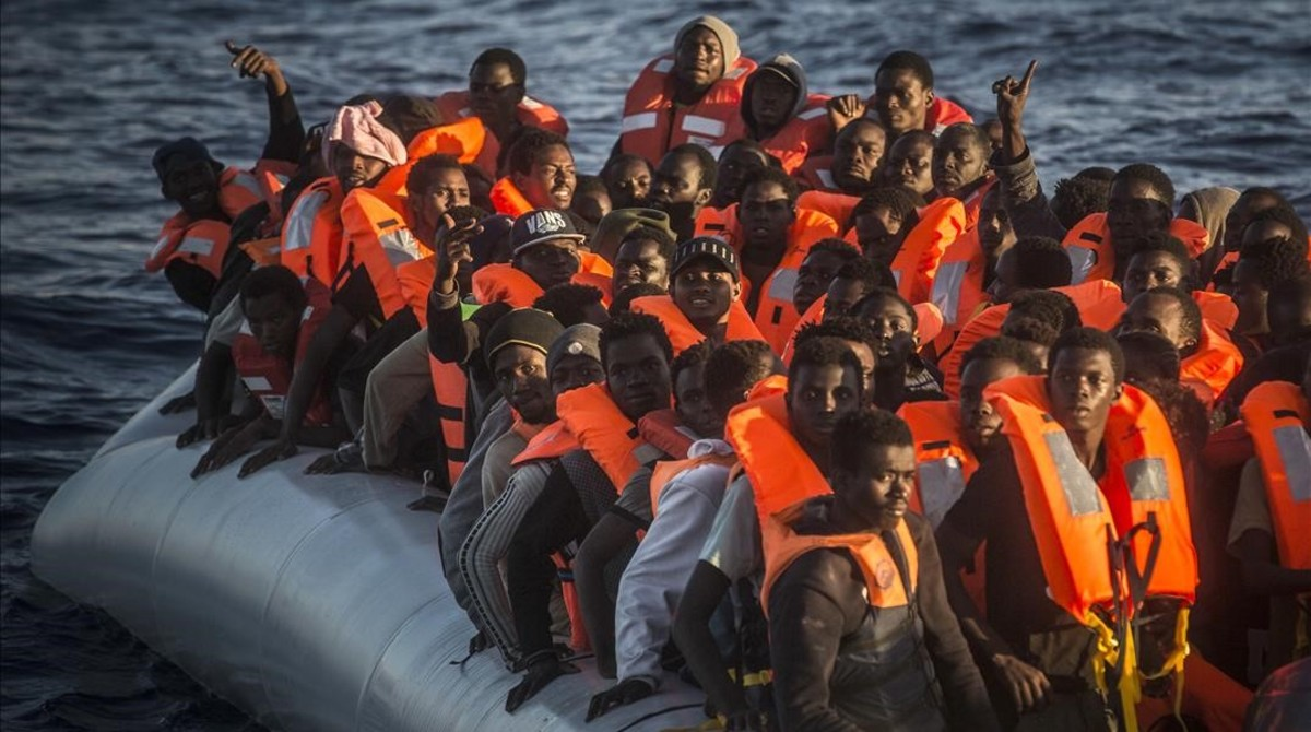 Sub-saharan refugees and migrants on an overcrowded dinghy wait to be rescued by a team of the Spanish NGO Proactiva Open Arms  24 miles north of Sabratha  Lybia  inside the so called Search and Rescue zone SAR  early in the morning on Tuesday  July 19  2016   AP Photo Santi Palacios