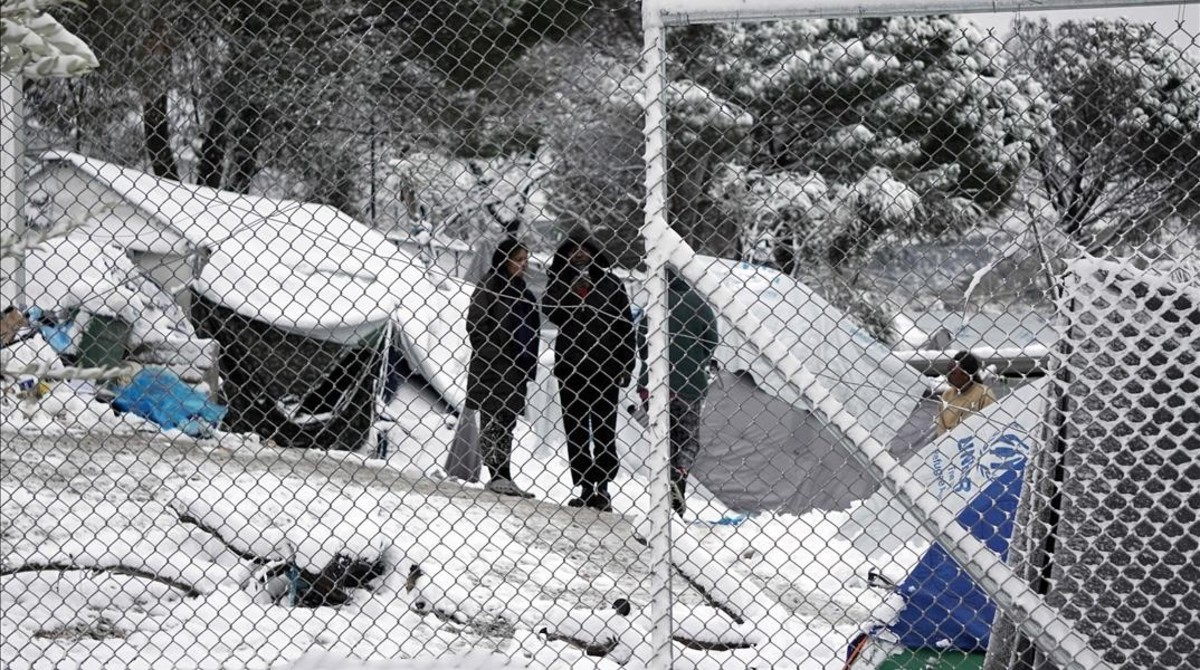 Migrants stand next to their tents at the Moria hotspot on the island of Lesbos following heavy snowfalls on January 7 2017 The number of migrants arriving in Europe by two main sea routes in 2016 plunged by almost two-thirds to 364 000 compared with the previous year EU border agency Frontex said Friday Frontex pointed to an EU border deal with Turkey which came into effect in March as having paved the way to a massive decline in the arrival of Syrian refugees and other migrants in Greece AFP PHOTO STR